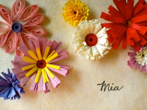 "red, pink, purple and yellow paper flowers on a card that says ""mia."""