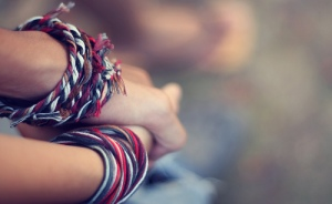 clasped hands with boldly colored thread twisted around each wrist.