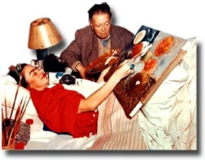 photgraph of frida laying in bed painting.  Diego Rivera is next to her, looking on and holding her palette.