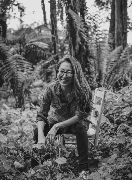 [Black and white photo of a korean woman smiling with long hair and glasses, sitting on a wooden chair with plants and trees all around her.]