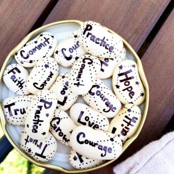 [photo of a jar lid filled with white large beans with black writing and designs on them. each bean has a different word on it: practice, courage, grow, trust, hope, faith, commit, love.]